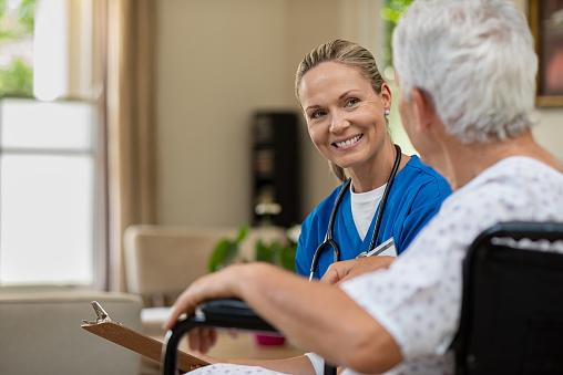 Friendly nurse talking to senior patient 1029340310