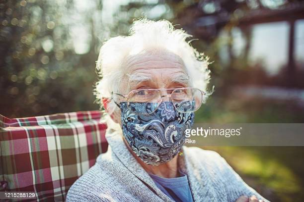 friendly old senior wears a mask to protect against viruses and bacteria - face masks imagens e fotografias de stock