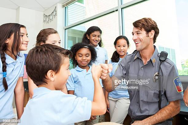 friendly police officer gives fist bump to student - police force stock pictures, royalty-free photos & images