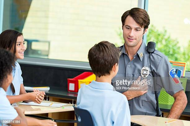 Friendly police officer shows student his badge