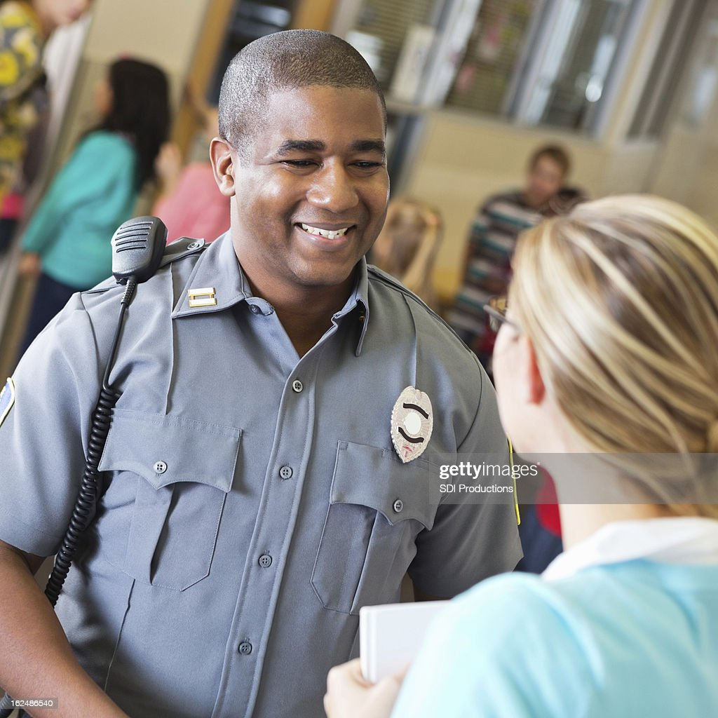 Friendly police officer talking with school teacher after safety demonstration : Stock Photo