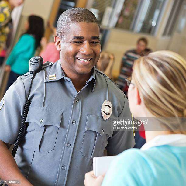 friendly police officer talking with school teacher after safety demonstration - police force stock pictures, royalty-free photos & images