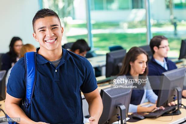 Friendly private high school student smiling in modern computer lab