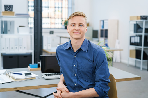 Friendly relaxed young businessman in the office 1146627237