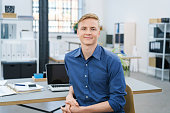 Friendly relaxed young businessman in the office