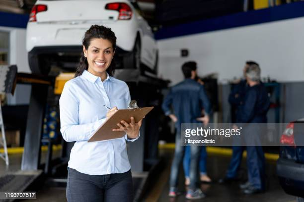 friendly sales assistant at a car workshop holding a list on clipboard smiling at camera - auto repair shop stock pictures, royalty-free photos & images