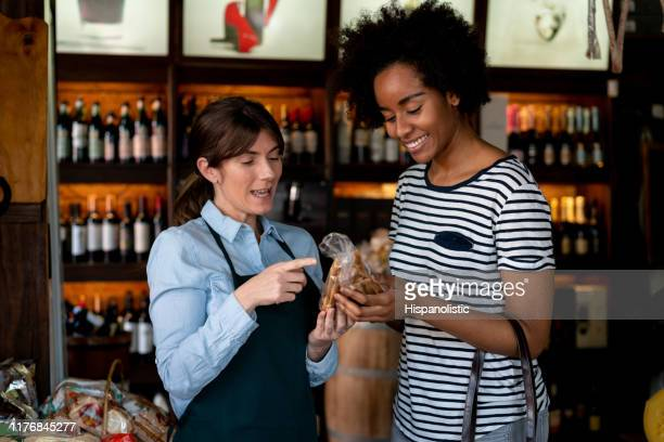 friendly sales clerk at the deli suggesting a product to female black customer - assistant stock pictures, royalty-free photos & images