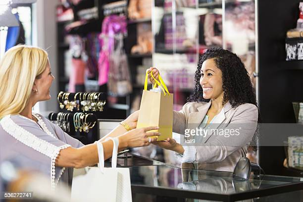 Friendly sales clerk with customer at checkout counter