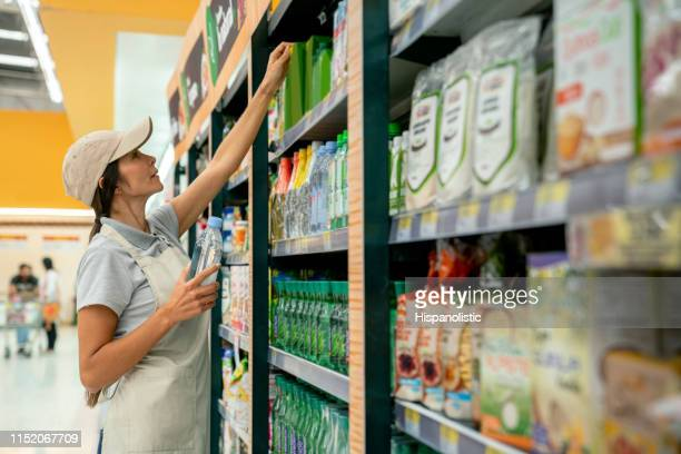 friendly sales woman reaching for a product on supermarket display - retail display stock pictures, royalty-free photos & images