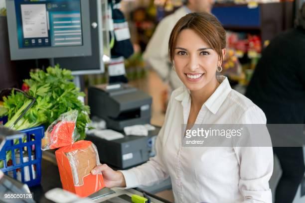 Freundliche Verkäuferin an der Kasse, Blick in die Kamera Lächeln beim Scannen von Barcodes auf Produkte