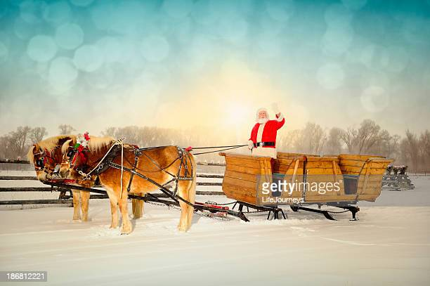 friendly santa waving to viewer with sleigh and horse team - sleigh stock photos and pictures