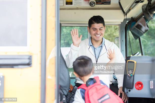 Friendly school bus driver greets young boy