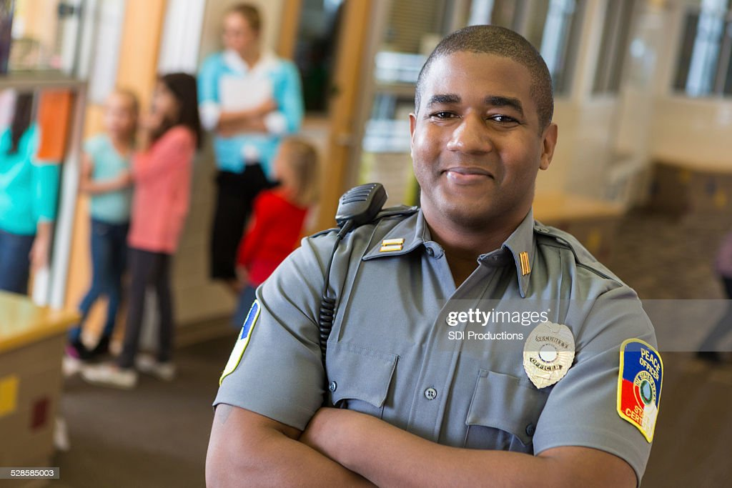 Friendly school security guard working on elementary school campus : Stock Photo