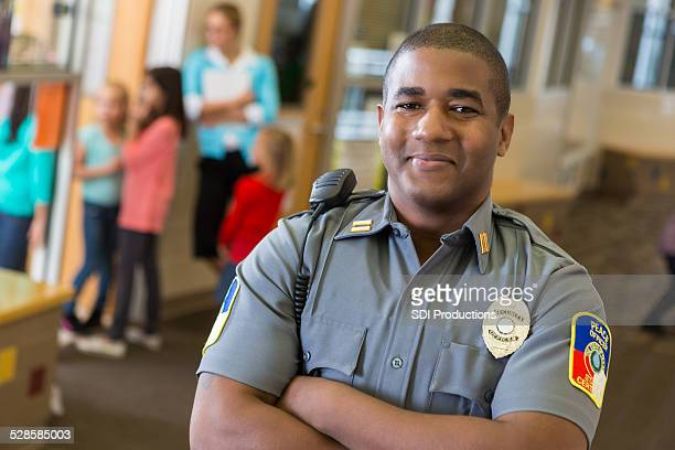 friendly school security guard working on elementary school campus - academy stock pictures, royalty-free photos & images