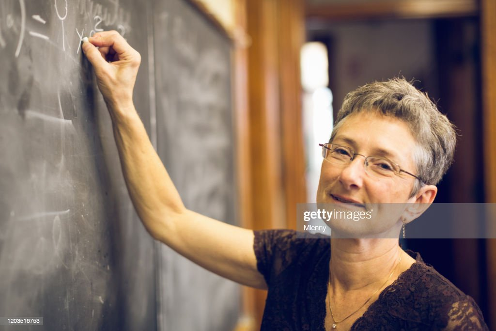 Friendly Senior Female Mathematics Teacher at Chalkboard : Stock Photo