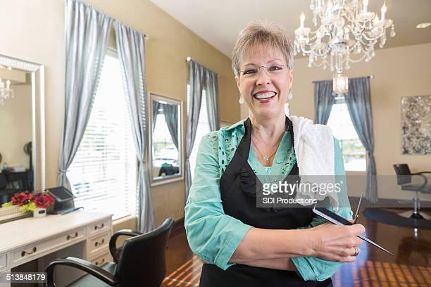 シニア hairstylist フレンドリーな笑顔で、アップスケールなサロンスタイルのお部屋