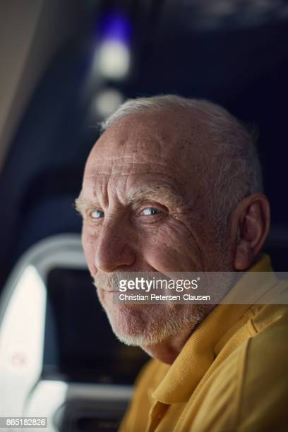 Friendly senior male 70+ traveling on airplane