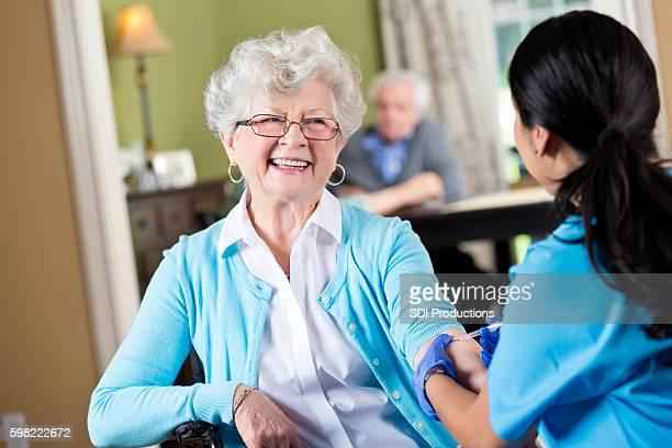 Friendly senior woman with home health care nurse