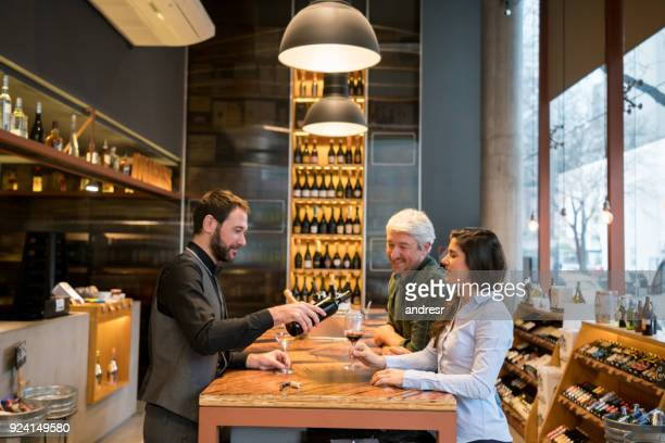 Friendly sommelier serving wine to a couple learning how to taste wine at a winery