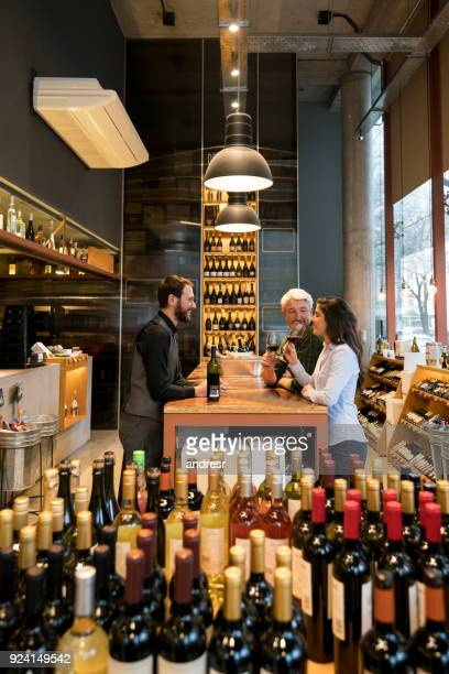 friendly sommelier teaching a couple about wine tasting at winery - bar drink establishment stock photos and pictures
