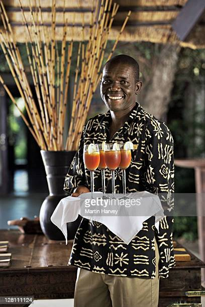 Friendly staff member serving welcome drinks to guests arriving at the ultra luxurious River Lodge. Lion Sands Private Game Reserve, South Africa.