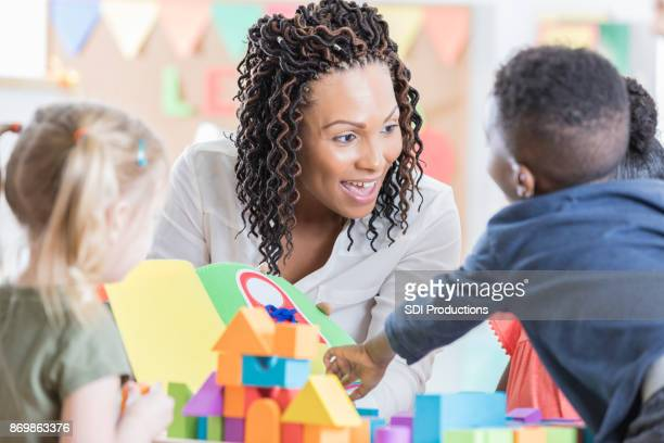 friendly teacher enjoys playing with her preschool students - preschool stock photos and pictures