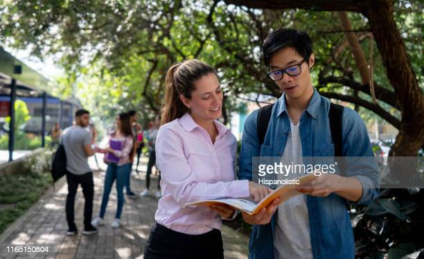 friendly teacher helping an exchange student at the college campus pointing at notebook while he pays attention - hispanolistic stock photos and pictures