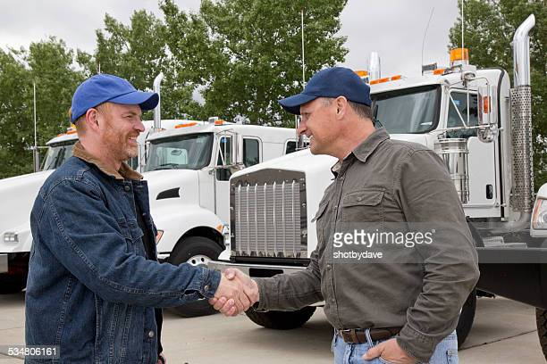 Friendly Trucker Handshake and Cooperation in Front of  Semi Truck