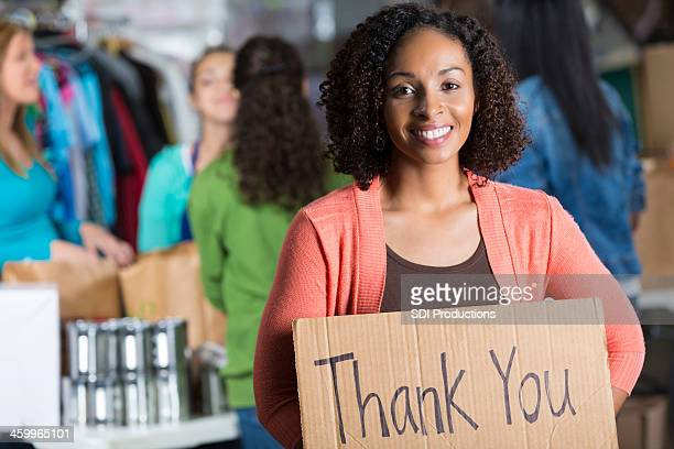 "Friendly volunteer holding """"thank you"""" sign at food bank"