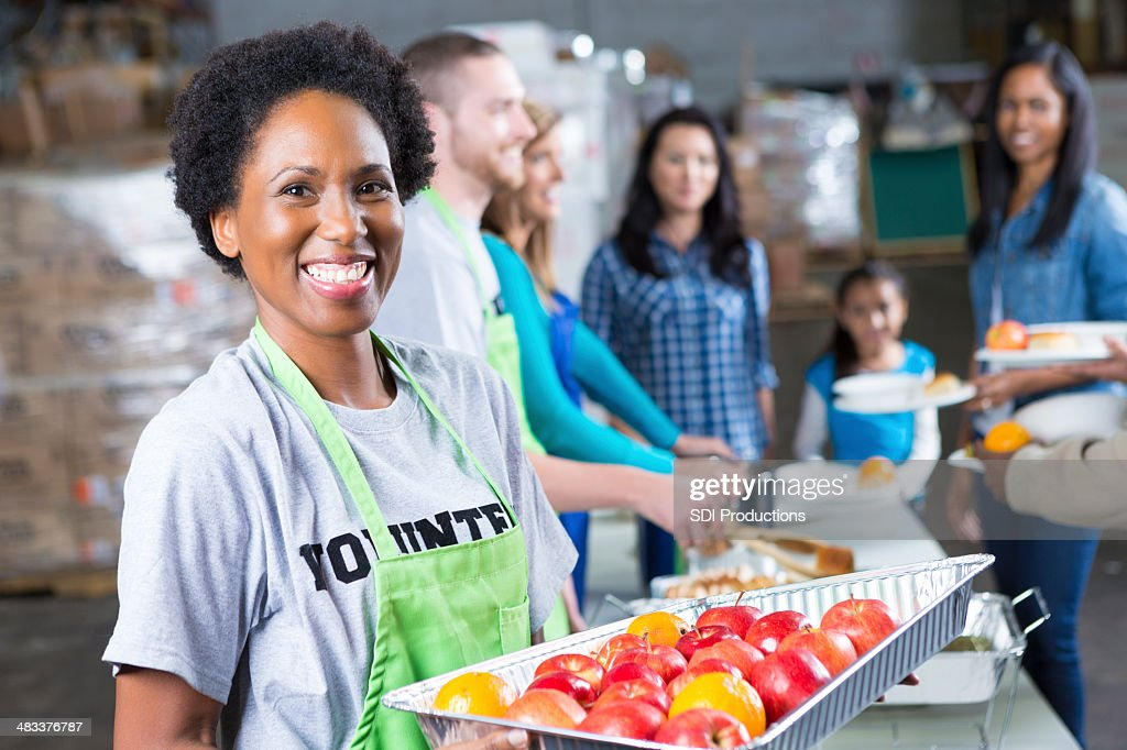 Friendly volunteer serving fresh fruit at community soup kitchen : Stock Photo