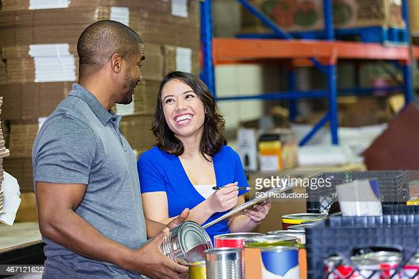 Friendly volunteers sorting canned food donations in charity warehouse