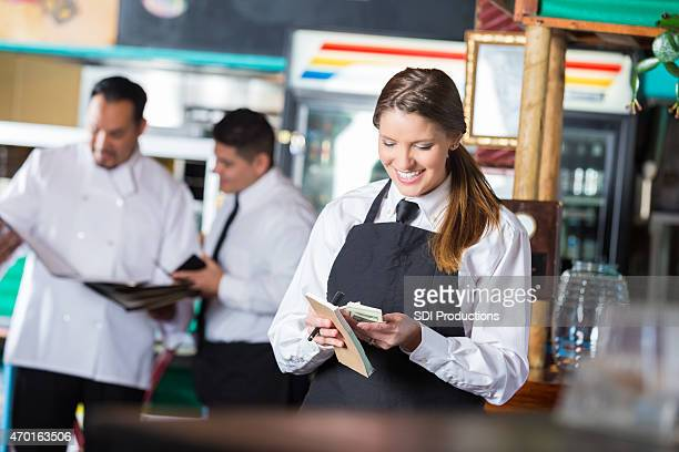 Friendly waitress in Tex-Mex restaurant counting tips after shift