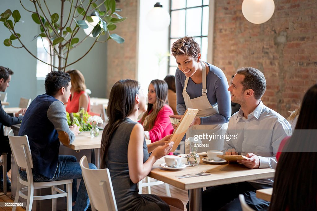 Friendly waitress serving couple at a restaurant : Stock Photo