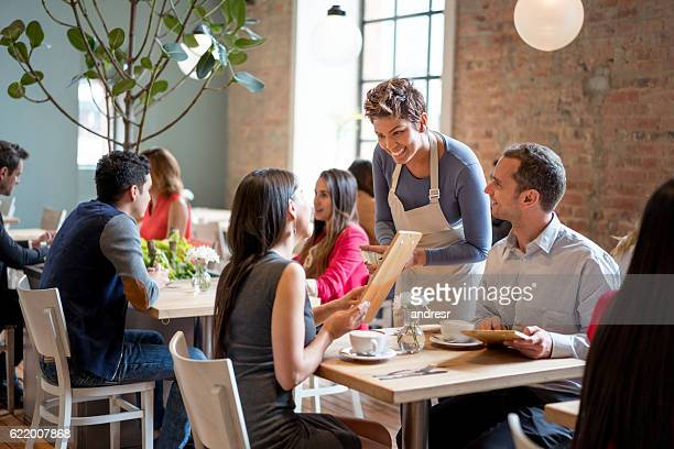friendly waitress serving couple at a restaurant - menu stock pictures, royalty-free photos & images