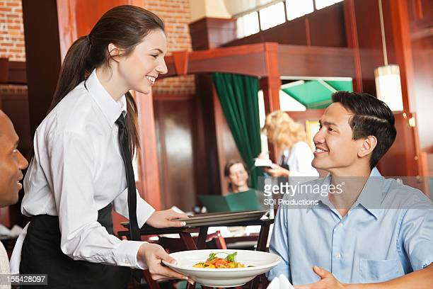 Friendly waitress serving food to guests at nice restaurant