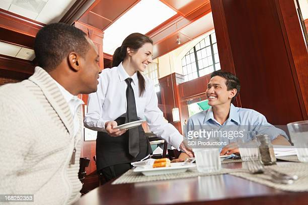 Friendly waitress serving guests in nice restaurant
