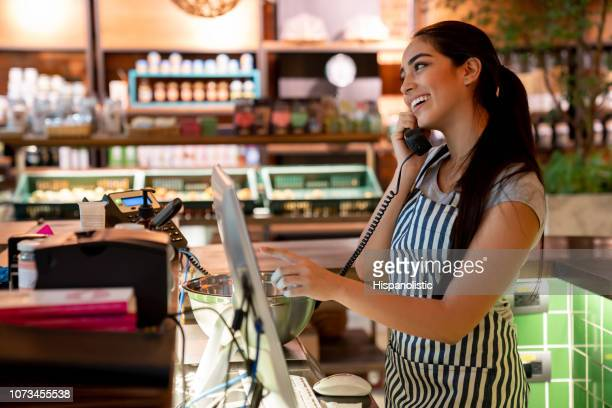 friendly waitress taking a take out order on phone while adding it to the system smiling - ordering stock pictures, royalty-free photos & images