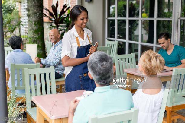 friendly waitress taking the order from an adult - hispanolistic stock photos and pictures