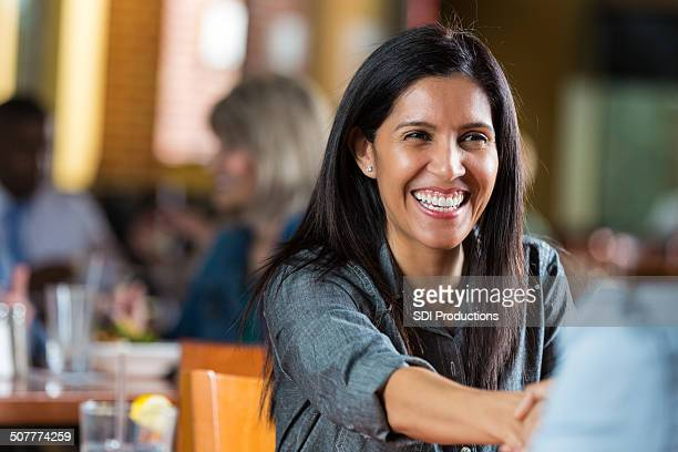 Friendly woman shaking hands during meeting in restaurant
