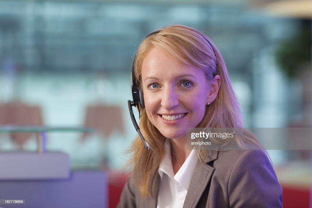 friendly woman with headset at helpdesk : Stock Photo