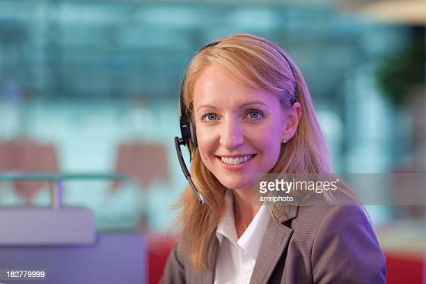 friendly woman with headset at helpdesk