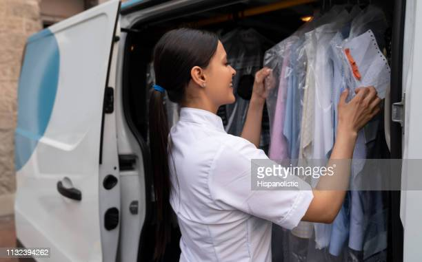 friendly woman working for a laundry service taking clothes to customers in delivery van - dry cleaned stock pictures, royalty-free photos & images