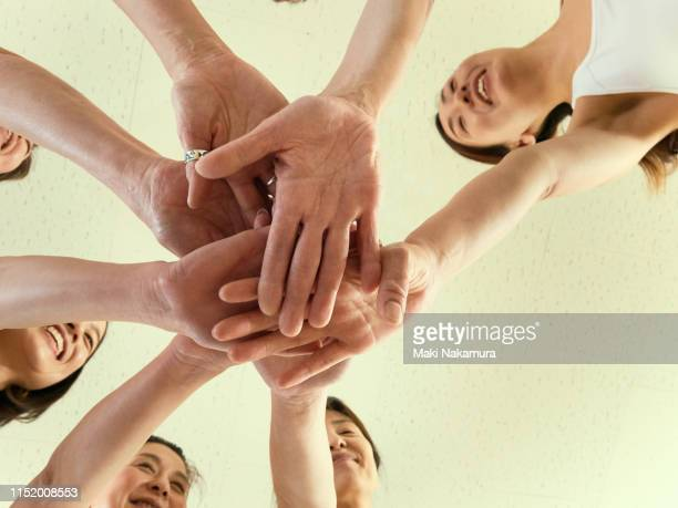 a friendly women dance team is united and piles up hands together - 絆 ストックフォトと画像