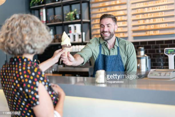 friendly worker at the ice cream parlor handing an ice cream to senior woman smiling - ice cream parlour stock pictures, royalty-free photos & images