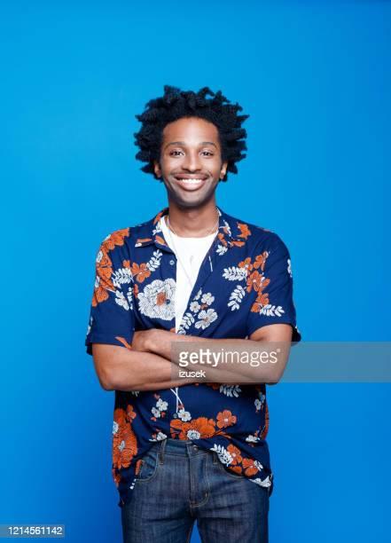 jeune homme amical dans la chemise hawaïenne sur le fond bleu - en manches courtes photos et images de collection