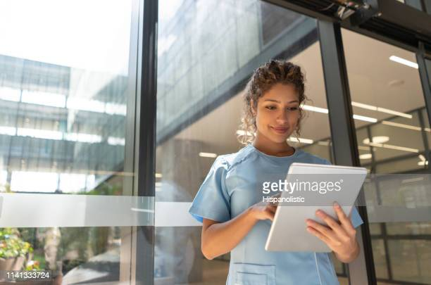 friendly young nurse looking at a medical chart on tablet slightly smiling - civilian stock pictures, royalty-free photos & images