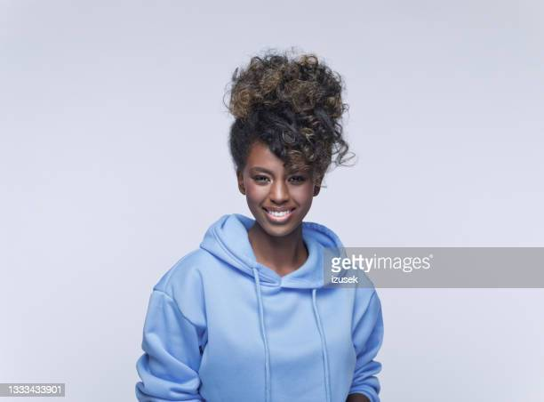 friendly young woman in blue hoodie - izusek stock pictures, royalty-free photos & images