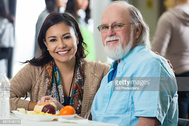friendly young woman volunteering to serve meal to seniors - depression bread line stock pictures, royalty-free photos & images