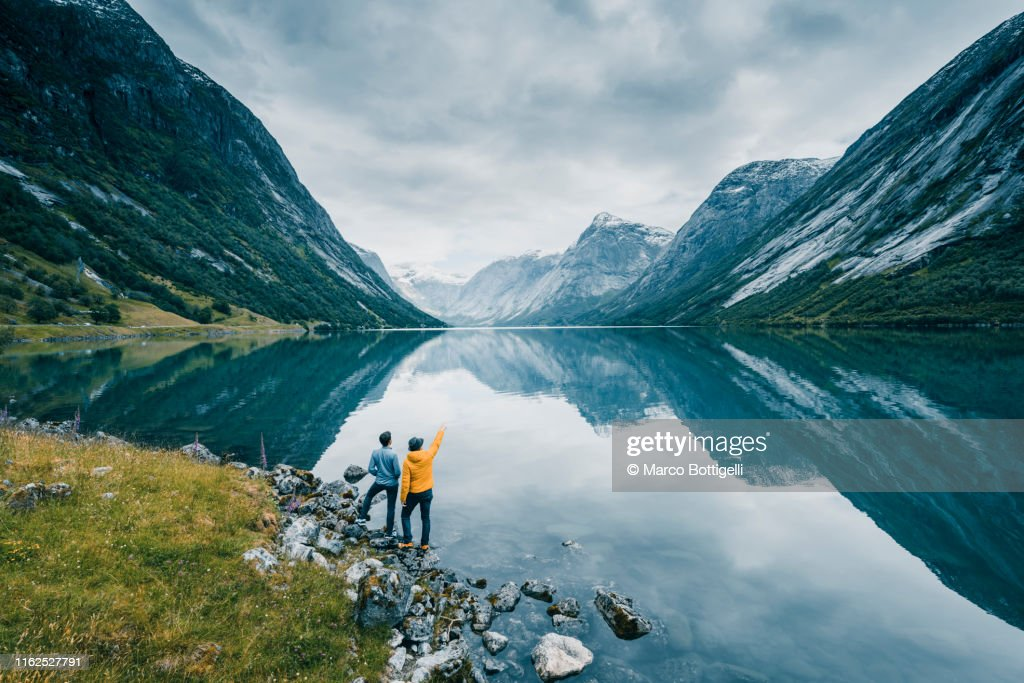 Friends admiring the view on the banks of a norwegian fjord, Norway : Stockfoto