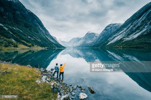 friends admiring the view on the banks of a norwegian fjord, norway - aspiraties stockfoto's en -beelden